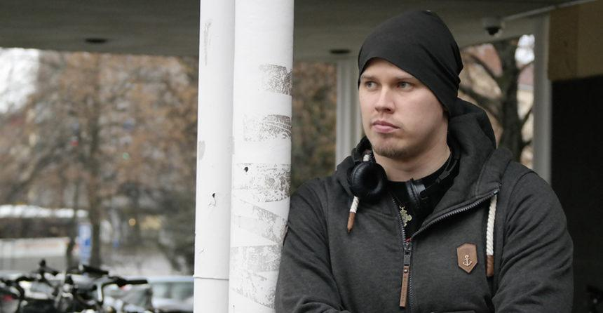 Ville Laitinen nojaa vakava ilme naamallaan JAMKin kampuksen parkkipaikalla pylvääseen ja katsoo oikealle. Sää on harmaa ja sateinen.